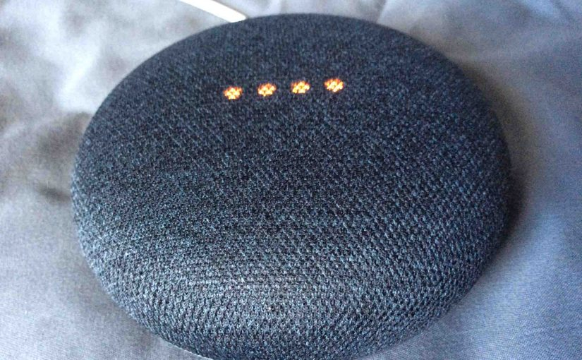 Picture of the Google Home Mini smart speaker, top front view, shown in muted mic mode.