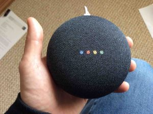 How to reset Google Home: Picture of the Google Home Mini speaker, displaying multi colored lights during reboot.