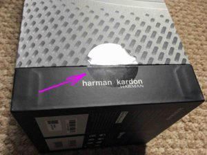 Picture of the Harman Kardon Invoke speaker, new in box, showing the sealing tape.