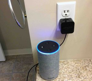 Picture of the Amazon Alexa Echo Gen 2 smart speaker with power adapter, plugged into wall outlet, showing the light-up ring Alexa feature.