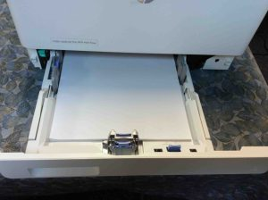 Picture of the HP LJ M477 printer, front view, showing lower paper tray open with white paper loaded.