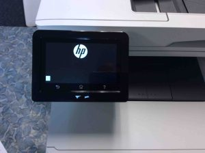 Picture of the HP Laserjet M477 printer, powering on and booting in progress, as seen on its control panel screen.