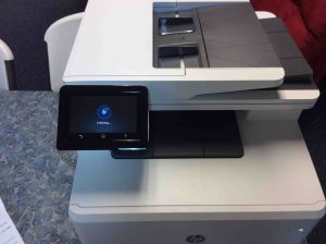 Picture of the Laserjet MFP M477 printer, front view, showing -Initializing- screen.