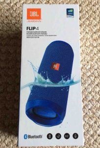 Picture of the JBL Flip 4 Bluetooth speaker box, front view, showing the speaker dipped in water. It's waterproof!
