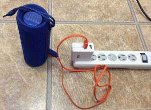Picture of the JBL Flip 4 wireless speaker, charging from a RavPower USB AC charger.