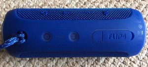 Picture of the JBL Flip 4 portable speaker, top view, showing speaker controls, showing the port door fully closed.
