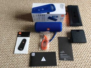 Picture of the JBL Flip 4 portable speaker, unboxed with its accessories laid out around this portable Bluetooth speaker.