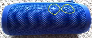 JBL Flip 4 reset button location. Picture of the JBL Flip 4 Bluetooth speaker. Showing the Volume UP and Play-Pause buttons circled in yellow.