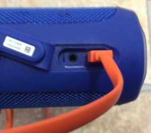 Picture of the JBL Flip 4 waterproof speaker with its orange micro USB charge cable inserted.