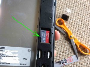 Picture of the Samsung Smart Phone J7 Galaxy Sky Pro, back view, showing a new microSD memory card positioned in slot but not yet snapped into place.