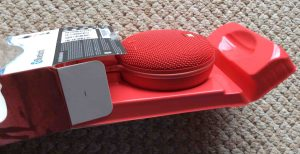 Picture of the JBL Clip 3 portable Bluetooth speaker package, showing the sliding out of the box contents.