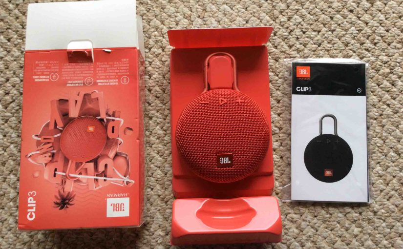 Picture of the JBL Clip 3 portable speaker package, unpacked, showing its contents.