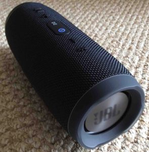 Picture of the JBL Charge 3 portable rechargeable speaker. Showing its left end. This Bluetooth speaker is powered on and paired.