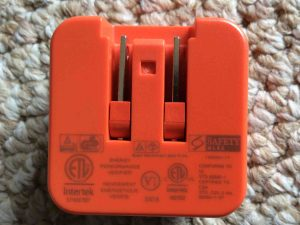 Picture of the Picture of a JBL AC power adapter, mains side view, Showing the safety labels. JBL Charge 3 charging.