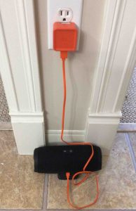 Picture of the JBL Charge 3 Bluetooth speaker, charging. Showing all connections for recharging this power bank speaker. The AC adapter is plugged Into wall, and connected to the speaker via the USB A to micro USB male charge cable.