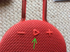 Picture of the JBL Clip 3 splashproof speaker, front view. Showing its Play-Pause button highlighted.