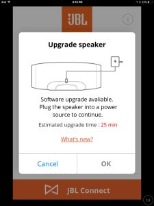Screenshot of the JBL Connect Plus app on iOS, prompting to plug in the speaker to AC power to update its firmware.