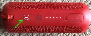 Picture of the JBL Flip 3 portable Bluetooth speaker, top view, power button glowing white, highlighted. Speaker powered ON.