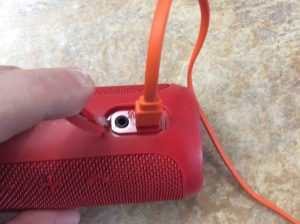 Picture of the JBL Flip 3 portable Bluetooth speaker, with the included USB charge cord connected. How to Charge JBL Flip 3 splashproof Bluetooth speaker.