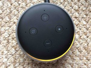 Picture of the Amazon Alexa Echo Dot 3rd Generation speaker, shown in Setup mode, light ring orange and spinning.