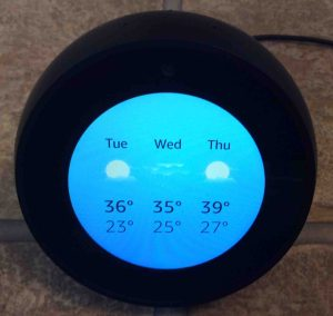 Picture of the Echo Spot speaker, front view, showing the local weather.