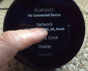 Picture of the Amazon Echo Spot speaker, displaying its Settings screen. Showing a finger swiping up to scroll down through the list of settings.