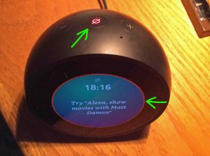 Picture of the Amazon Echo Spot talking speaker, top front view, showing the mics muted. The mute button and light ring on the screen are glowing red to indicate muting, and are highlighted.