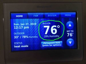 Picture of the Honeywell RTH9580WF smart thermostat, displaying its -Home- screen, showing the current indoor temperature to be 76 degrees, circled.