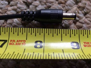 Picture of the JBL Xtreme AC adapter, showing its DC output jack laying against a ruler.