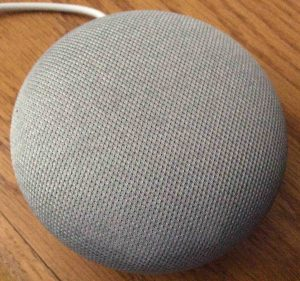 Picture of the Google Home Mini speaker, gray model, top view, with all lights OFF.