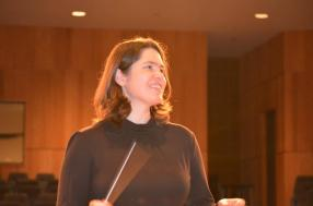 A photograph of Lori conducting a musical piece