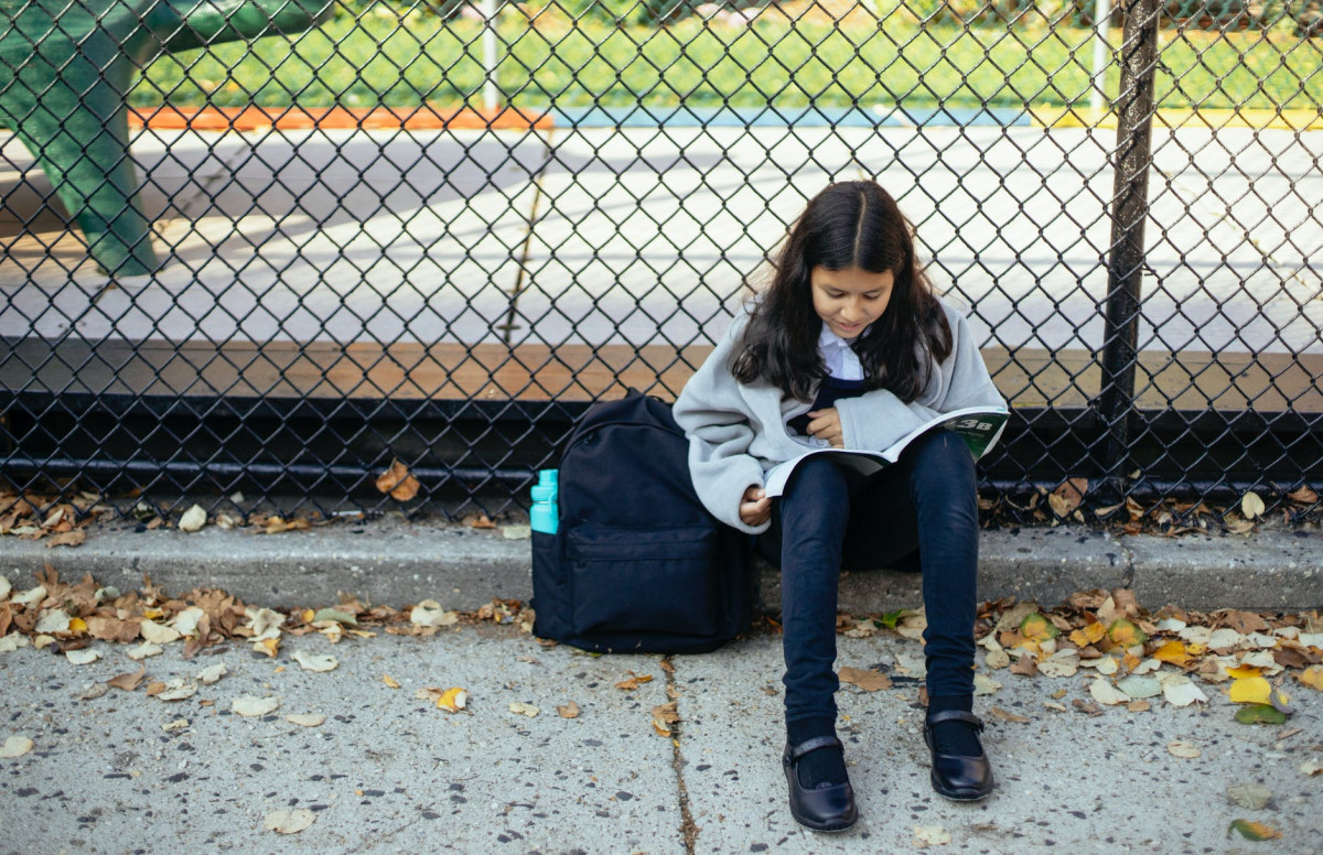 focused girl reading textbook on street