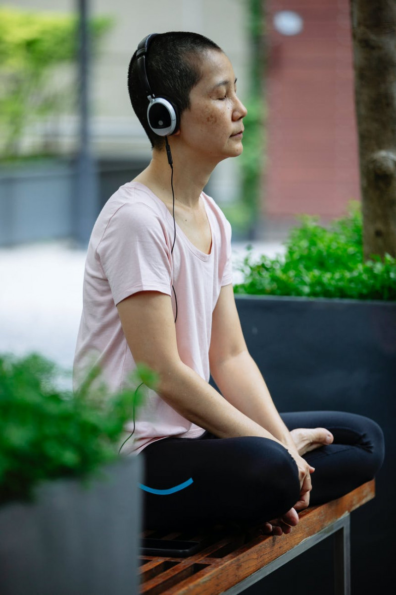 calm ethnic woman meditating in padmasana pose with closed eyes