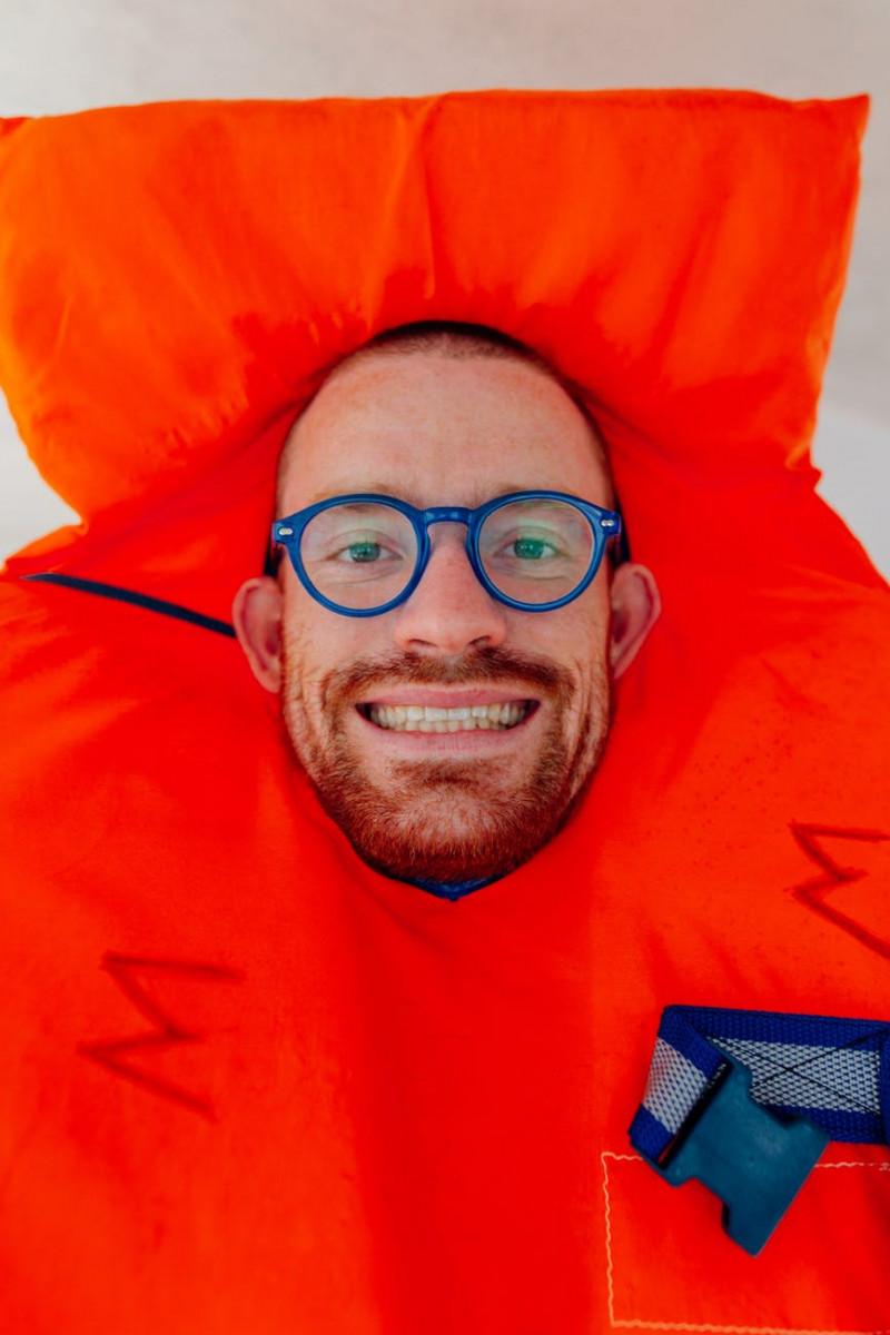 smiling man wearing blue framed eyeglasses