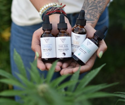 hands holding tonic cbd bottles hemp-farm