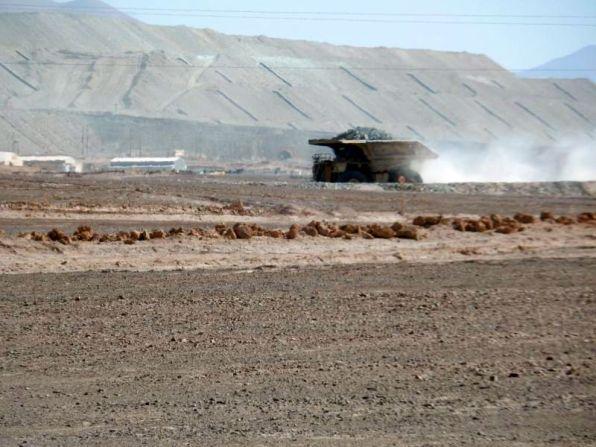 In der Kupfermine ist Kolonnenverkehr von Muldenkippern. Riesige künstliche Berge werden aufgeschüttet.