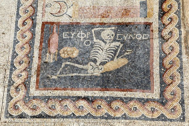 "HATAY, TURKEY - APRIL 20: 2,400 year-old mosaic, discovered during excavations, saying ""Be cheerful, enjoy your life"" in Ancient Greek language is seen in southern Hatay province of Turkey, on April 20, 2016. Mosaic depicts lying down skeleton with a jorum in his hand together with a wine pitcher and bread. (Photo by Halit Demir/Anadolu Agency/Getty Images)"