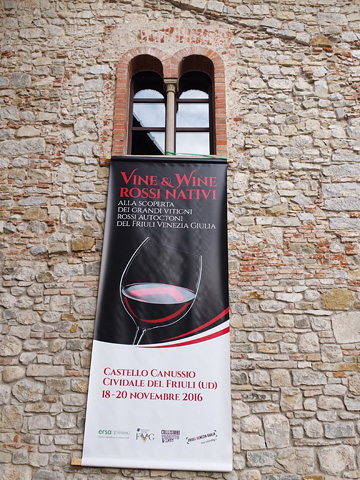 banner for Vine & Wine Rossi Nativi hanging from romanesque double-arched window high on stone wall