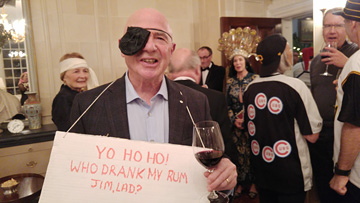 Tony wearing an eye patch and a sign that says YO HO HO! WHO DRANK MY RUM JIM, LAD?