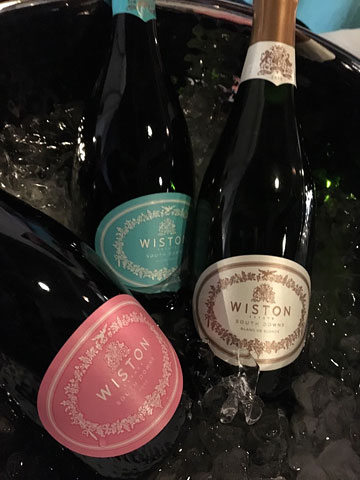 three bottles of Wiston Estate wines in an ice bucket; the labels are pink, blue, and ivory, respectively