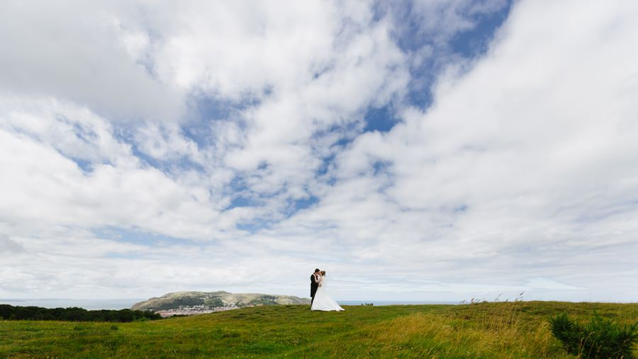 bride and groom on Nant y gamar with grat orme in background. Get married in North Wales