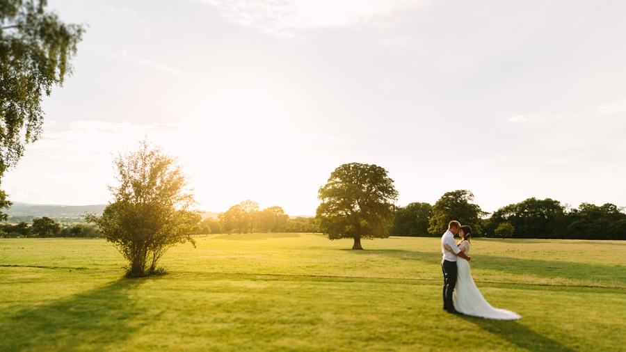 bride and groom embrace in the sunset at Pentre Mawr. Get married in North Wales
