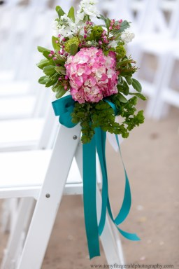 Pink hydrangeas on chairs as wedding decorations