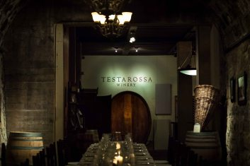 Testarossa winery cave with table setting and wine barrel.