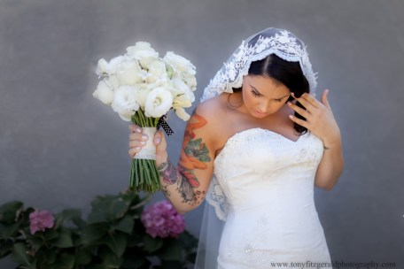 bride wearing a Spanish Mantilla veil and holding a bouquet looking down