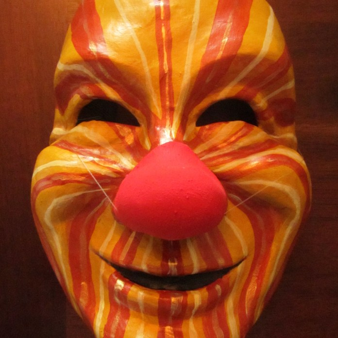 The mask is painted so that the rays of the sun emanate from the nose of the clown, spreading warmth and joy.