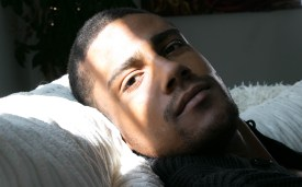 Portrait of a handsome, good looking black man lying on armchair and looking at camera.