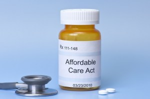 Affordable Care Act prescription bottle on blue with sethescope and pills.