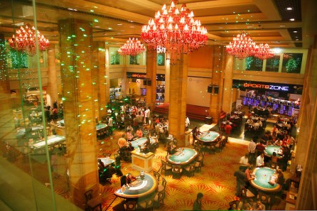 Phnom Penh's Nagaworld Casino and five-star hotel is one of Cambodia's biggest private employers with more than 3,000 staff catering for a stream of visitors. It functions non-stop 24 hours a day with an inside airconditioned controlled temperature of 21 degrees.It is a 14 storey hotel and entertainment complex, with more than 500 bedrooms, 14 restaurants and bars, 700 slot machines and 200 gambling tables. There is also a spa, karaoke and VIP suites, live bands, and a nightclub. Its monolithic building dominates the skyline at the meeting point of the Mekong and Tonle Sap rivers, in stark contrast to nearby intricate Khmer architecture.///Birds eye view over casino and gaming halls at Nagaworld showing guests gambling and architectural features
