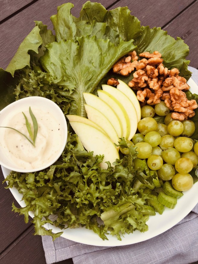 a bowl of green salad with creamy dressing on the side